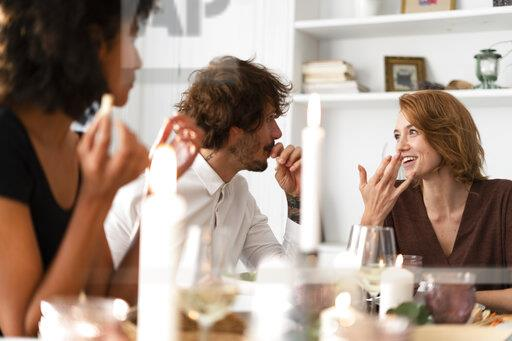 Friends having fun at a dinner party, enjoying eating together