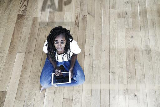 Portrait of smiling woman sitting on the floor with digital tablet