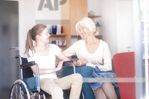 Daughter in a wheelchair with her mother, smiling
