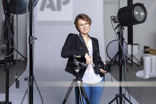 Portrait of smiling young photographer with equipment at photographic studio