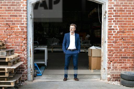 Businessman standing at old warehouse looking away