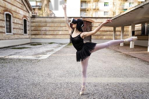 Italy, Verona, Ballerina dancing in the city wearing VR glasses