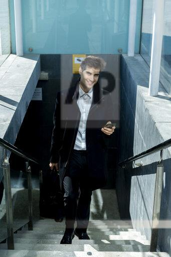 Smiling businessman with cell phone walking up stairs in the city