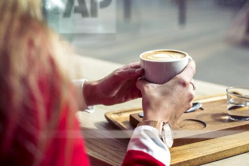 Woman's hands holding cup of coffee, close-up