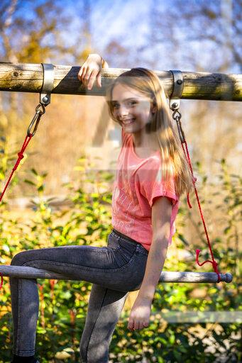 Portrait of smiling girl sitting on gymnastic bar in the garden