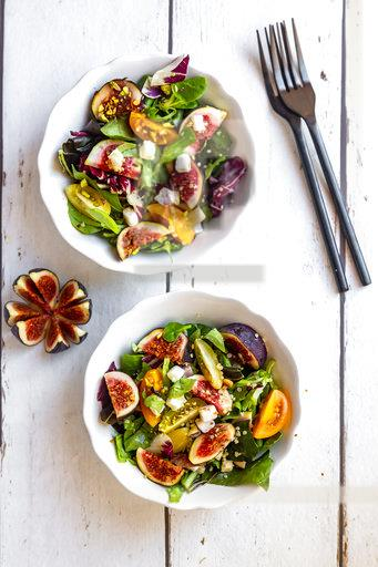 Mixed salad with fig, tomato, ham, cheese, pistachio