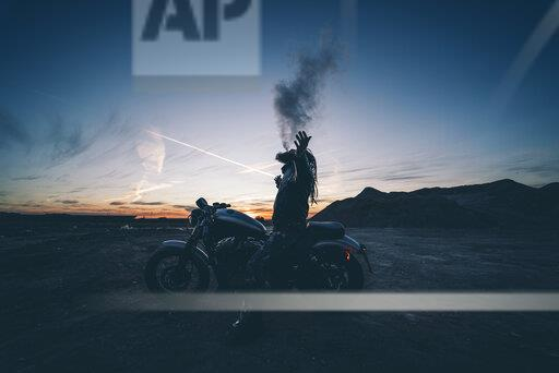 Bearded man with dreadlocks sitting on motorbike at sunset smoking electronic cigarette