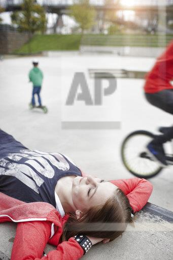 Teenage girl lying on a wall at a skatepark