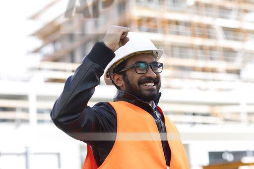 Portrait of happy construction engineer in front of construction site wearing hard hat and safety vest