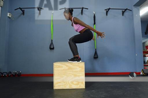 Woman practicing in a gym doing a box jump
