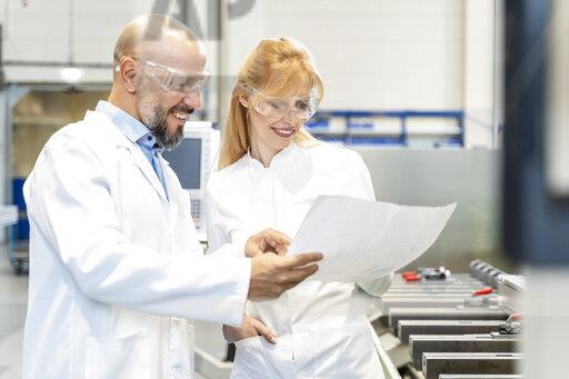 Two happy technicians wearing lab coats and safety glasses looking at plan in factory