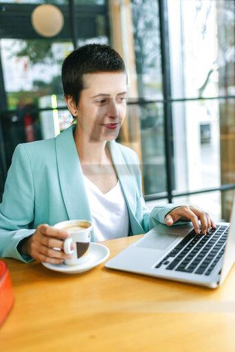 Woman in bar with laptop and cup of coffee