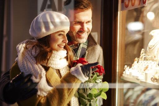 Smiling couple looking in shop window of jewellery store at Christmas time