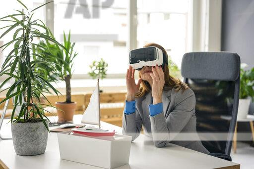 Businesswoman sitting at desk with a ship model, looking through VR glasses