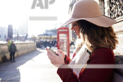 UK, London, woman in the city wearing a floppy hat using cell phone