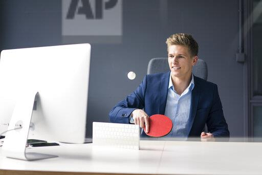 Young businessman sitting at desk in office playing table tennis