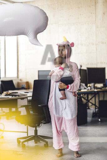 Young mother in unicorn onesie, holding her son in her arms, with speech bubble over her head