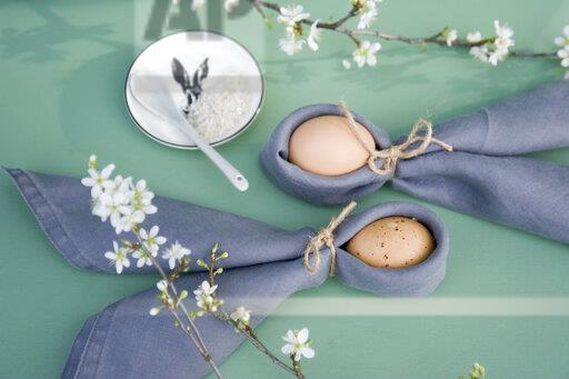 Easter decoration, Twigs of sloe, napkins with Easter eggs, folded as rabbit ears