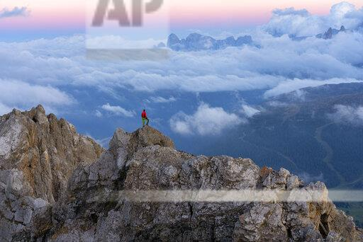 Italy, Veneto, Dolomites, Alta Via Bepi Zac, mountaineer standing on Pale di San Martino mountain at sunset