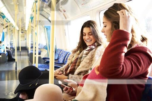 UK, London, two happy women in underground train using cell phone