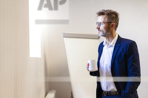Businessman holding cup of coffee in office