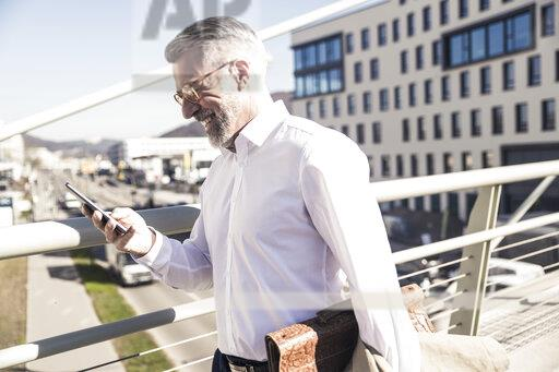 Smiling mature businessman using cell phone in the city