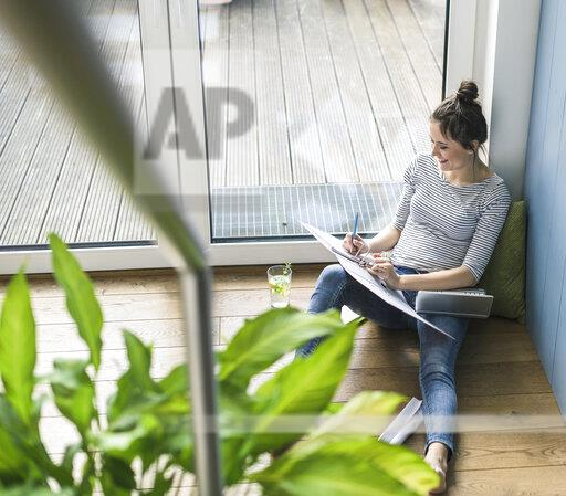 Bird's eye view of smiling woman sitting at the window at home working with laptop and file folder