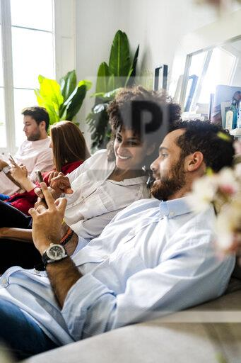 Friends sitting on couch, working casually together, using smartphones