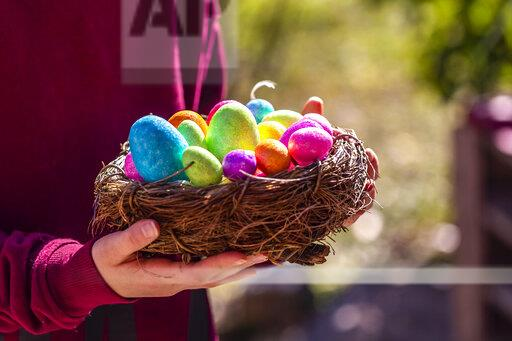 Girl holding Easter nest with colorful Easter eggs