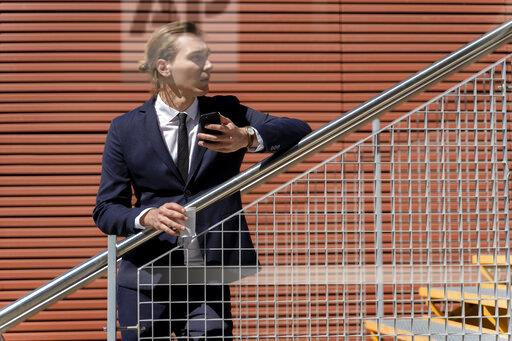 Young businessman holding smartphone and takeaway coffee outdoor