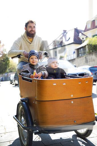 Happy father with two children riding cargo bike in the city
