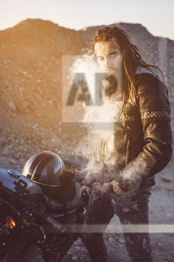 Portrait of bearded biker with dreadlocks smoking electronic cigarette