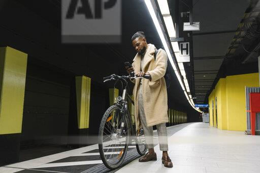 Stylish man with a bicycle and smartphone waiting for the metro
