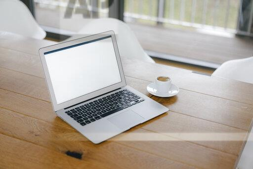 Laptop on desk in office with cup of espresso