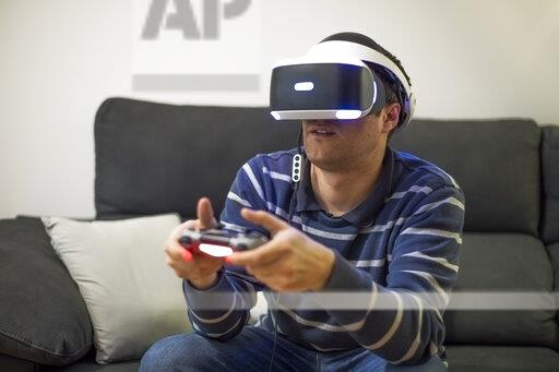 Young man wearing VR glasses sitting on couch at home playing video game