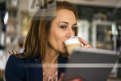 Businesswoman working in coffee shop, using digital tablet, drinking coffee