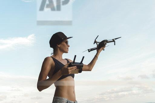 Woman holding drone under sky with clouds