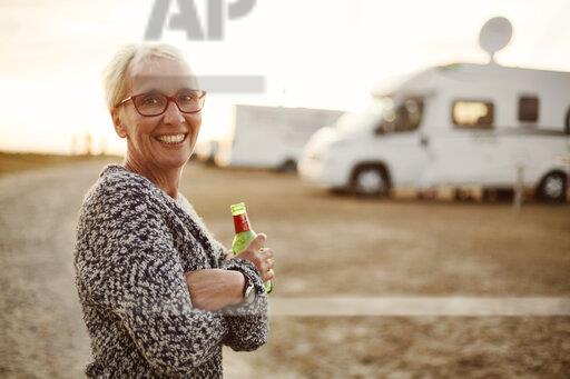 Portrait of smiling woman with beer bottle on camping ground in the evening