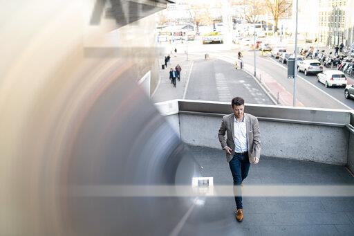 Businessman walking on overpass in the city