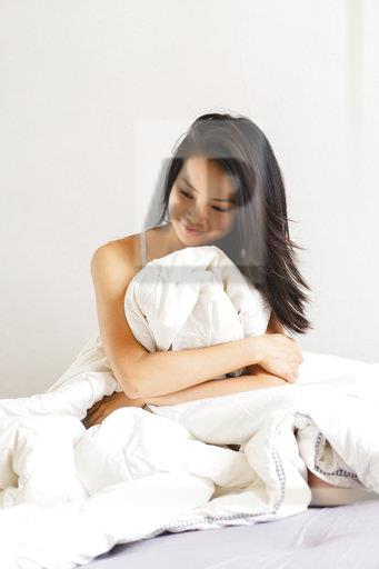 Smiling young woman sitting in bed