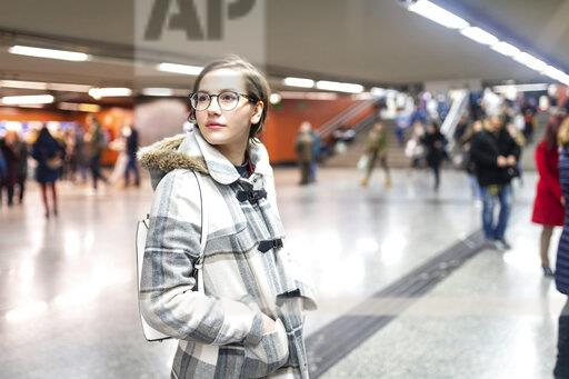 Spain, Madrid, young woman in a busy metro station