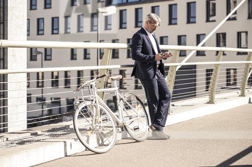 Mature businessman with bicycle using cell phone in the city