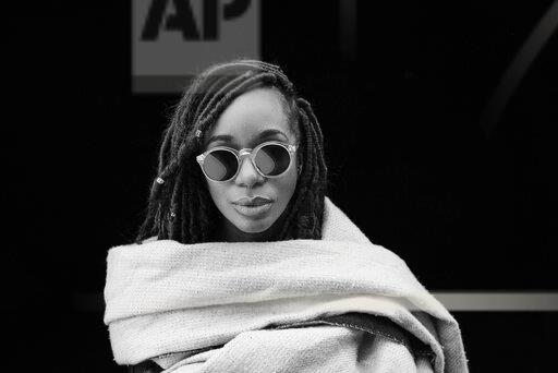 Portrait of woman with dreadlocks wrapped in blanket in front of black background