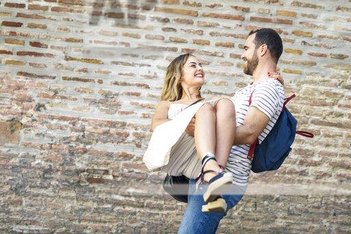Happy man with backpack carrying girlfriend at brick wall
