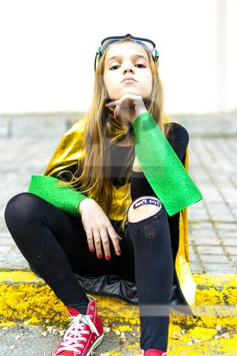 Girl posing in super heroine costume sitting on curb