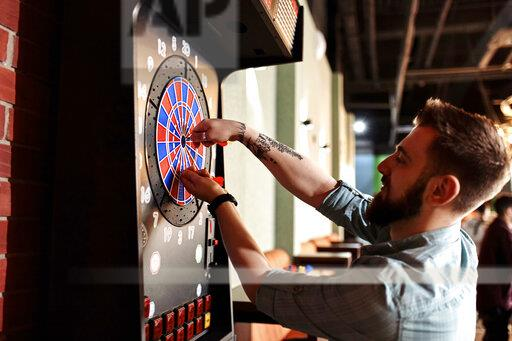 Man taking out darts from electronic dartboard
