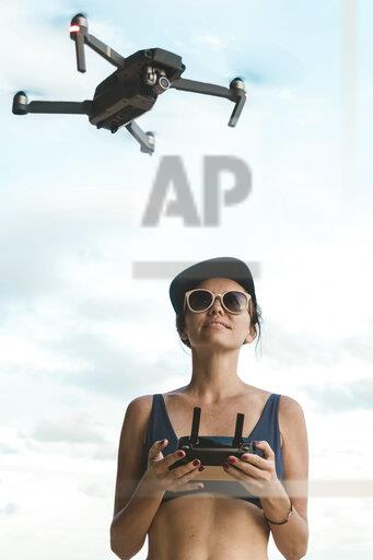Woman flying drone under sky with clouds