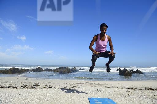 Sportive woman jumping on the beach