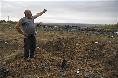Local resident Viktor stands on shell crater on the Malaysia Airlines Flight 17 plane crash side, near village of Hrabove, eastern Ukraine, Tuesday, Sept. 9, 2014. (AP Photo/Sergei Grits)