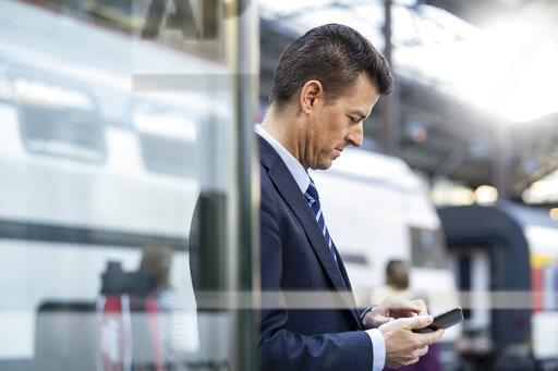Businessman using cell phone at train station